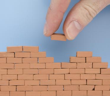Hand_Placing_Small_Brick_on_Wall.jpg